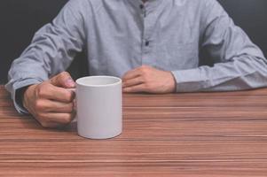 man met een koffiekopje aan zijn bureau