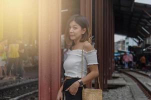 Aziatische vrouw die zich voordeed op de treinrails foto