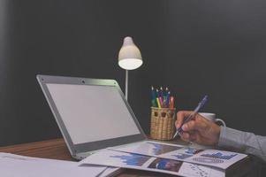 zakenmensen zitten op het werk en controleren documenten aan het bureau in de kamer foto