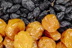 bovenaanzicht van gedroogde kersenpruimen met zwarte rozijnen