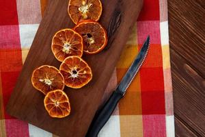 bovenaanzicht van gedroogde stukjes sinaasappel met keukenmes op een houten snijplank op geruite tafellaken