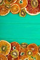 bovenaanzicht van gedroogde grapefruit en stukjes sinaasappel met gedroogde kiwi op groene houten achtergrond met kopie ruimte