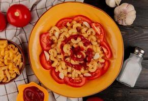 bovenaanzicht van macaroni pasta in plaat met tomaten ketchup zout knoflook en macaronis op doek en houten achtergrond