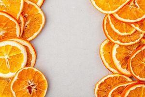 bovenaanzicht van gedroogde stukjes sinaasappel gerangschikt op een witte achtergrond met kopie ruimte foto