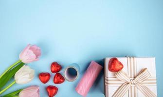 bovenaanzicht van roze kleur tulpen hartvormige chocolade snoepjes verpakt in rode folie, geschenkdoos en rol van kleurrijk papier op blauwe achtergrond met kopie ruimte
