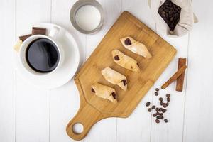 bovenaanzicht van bloemkoekjes met aardbeienjam op een houten bord met een kopje koffie op witte achtergrond