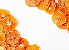 bovenaanzicht van gedroogde stukjes sinaasappel gerangschikt op een witte achtergrond met kopie ruimte