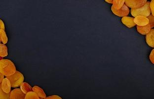 bovenaanzicht van gedroogde abrikozen op zwarte achtergrond met kopie ruimte foto