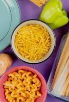 bovenaanzicht van macaronis als cavatappi bucatini tagliatelle met peper en plaat op paarse achtergrond