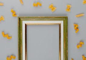 bovenaanzicht van macaronis als farfalle fusilli penne rond frame op blauwe achtergrond met kopie ruimte
