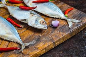 makreel vis op houten snijplank foto