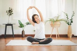 vrouw die yoga thuis doet foto