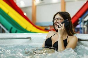het mooie meisje, zittend in het zwembad en praten aan de telefoon