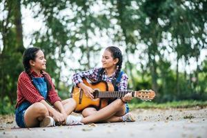 twee meisjes ontspannen en gitaar spelen foto