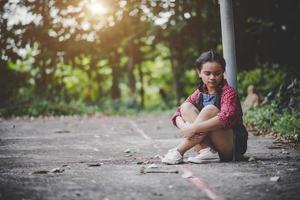 verdrietig meisje, zittend in een park foto