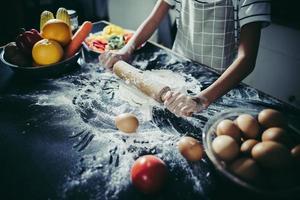 kleine chef-kok die deegroller gebruikt om het deeg uit te rekken foto