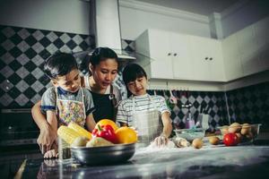 moeder leert haar kinderen hoe ze pizzadeeg moeten bereiden foto