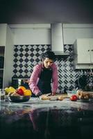 man kneden zelfgemaakte pizzadeeg in de keuken foto