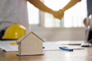 twee mensen die elkaar de hand schudden en een huis bouwen foto