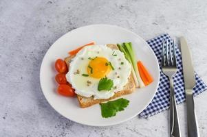 een gebakken ei op toast gegarneerd met peperzaadjes met worteltjes en lente-uitjes