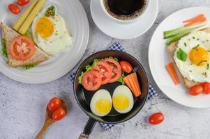 gekookte eieren, wortelen en tomaten met lepel en koffiekopje