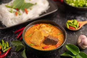 kip curry in een zwarte kop met rijstnoedels