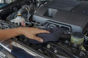 monteur controleert en reinigt de motor van de auto