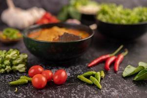 kipcurry in een zwarte kop, compleet met tomaten en chili