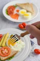 vork reiken naar gebakken eieren met brood met groenten als ontbijt