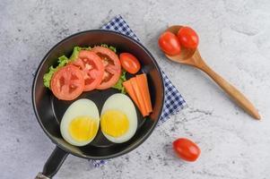 gekookte eieren, wortelen en tomaten in een pan met tomaten