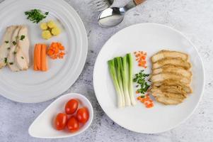 gestoomde kipfilet op een witte plaat met lente-uitjes en wortelen