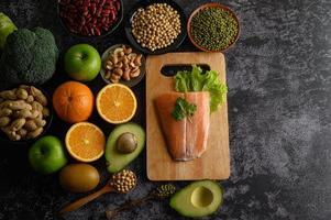 peulvruchten, fruit en zalmvissen op een houten snijplank foto