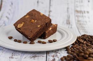 chocoladetaart op een witte plaat en koffiebonen foto