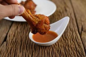 hand met een stuk gebakken kip met saus