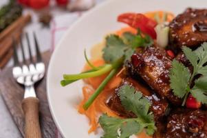 zoet varkensvlees met chili, lente-uitjes, wortelen en koriander foto