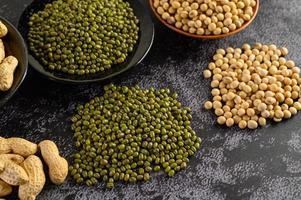 sojabonen, pinda's en groene bonen op een zwarte cementvloer achtergrond