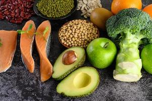 peulvruchten, broccoli, fruit en zalm op een zwarte cementachtergrond foto