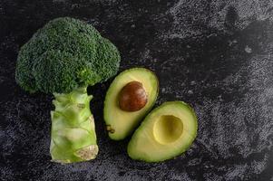broccoli en avocado op de zwarte achtergrond van de cementvloer foto