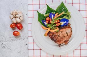varkenssteak met tomaat, wortel, rode ui, pepermunt, vlindererwtenbloem en limoen