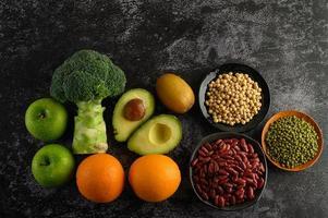 broccoli, appel, sinaasappel, kiwi, avocado en bonen op een zwarte cementvloer achtergrond foto