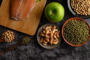 peulvruchten, fruit en zalm op een zwarte cementachtergrond