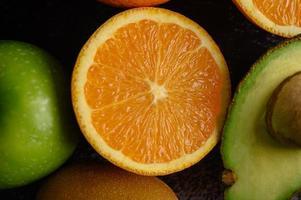 heldere close-up schijfje verse oranje appel, kiwi en avocado foto