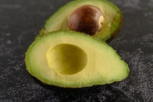 gehalveerde avocado op zwart cement foto