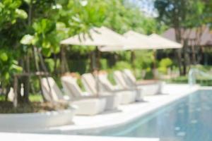 wazig zwembad en witte stoelen foto