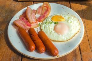 spek, gebakken eieren en worst op witte plaat en houten tafel