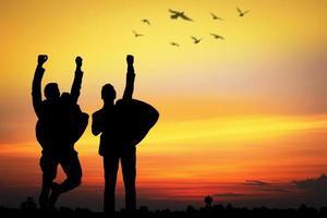 silhouet van mensen juichen bij zonsondergang