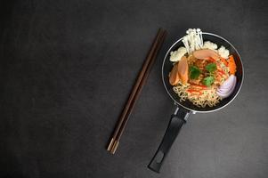 stilleven met noedels in een pan en eetstokjes foto