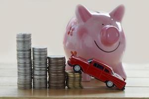 stapels munten met speelgoedauto en spaarvarken foto