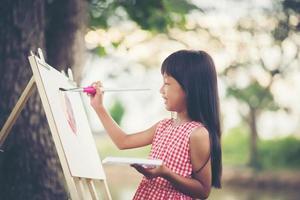 klein meisje kunstenaar schilderen van een foto in het park