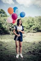 jong meisje met kleurrijke ballonnen in de natuur